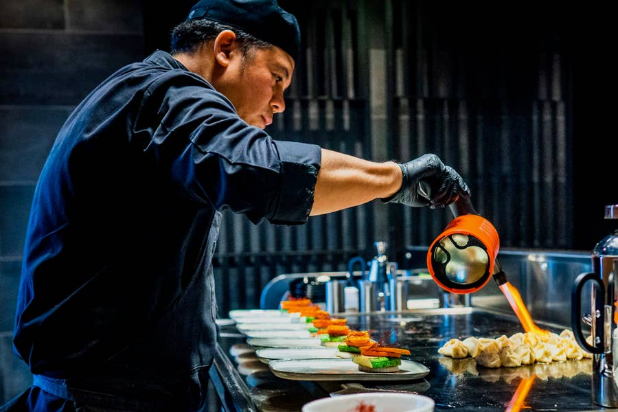 Chef using a blowtorch in a commercial kitchen