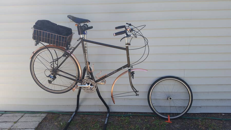 A bicycle on a bike stand with the front wheel removed