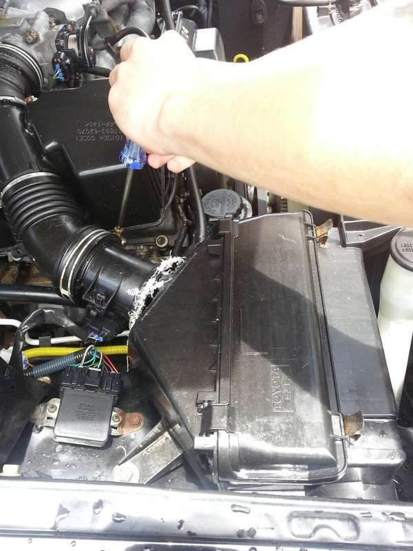 Disconnect all hoses from the air filter housing