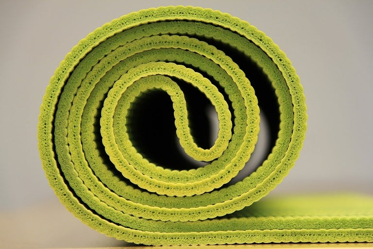 Yoga mat half rolled.