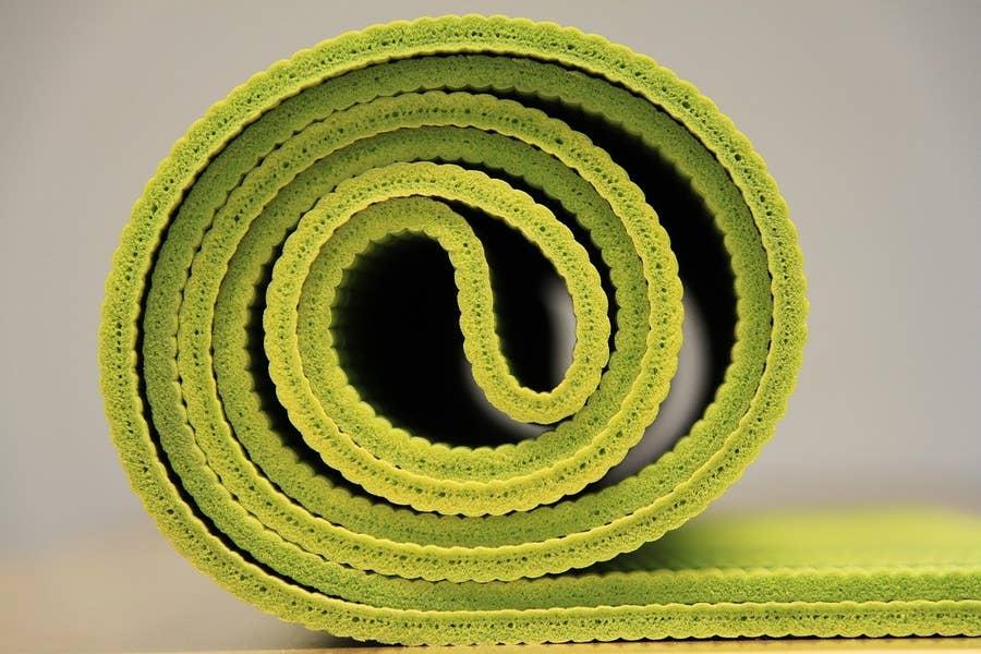 Yoga mat half rolled.