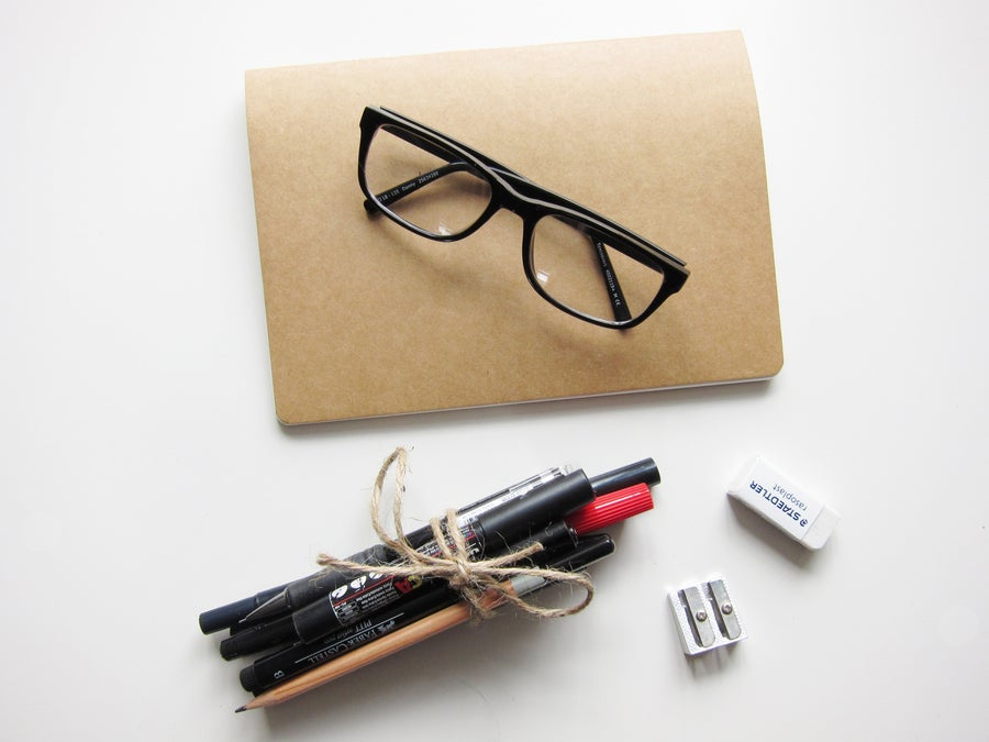 Book with glasses, pens and pencils