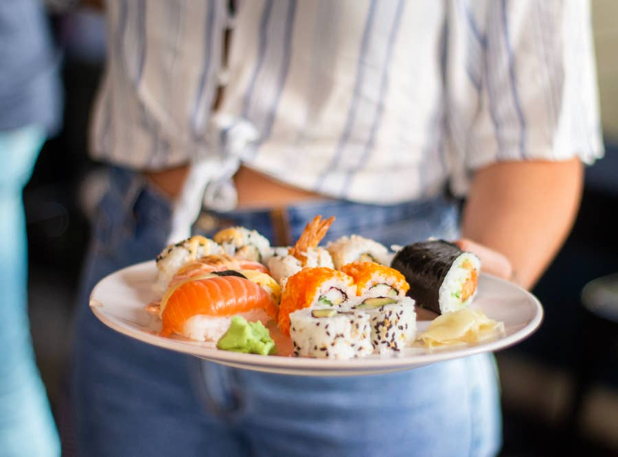 A woman holding a plate of sushi