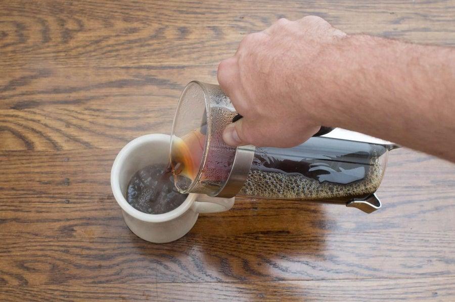 pouring french press coffee into a mug