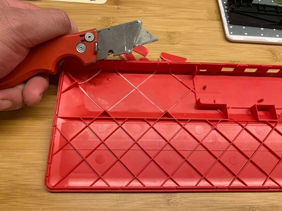 A box cutter cutting pieces from the Raspberry Pi keyboard