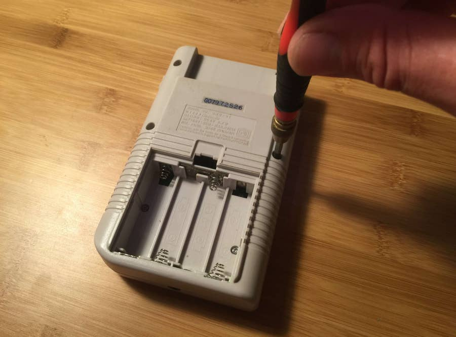 A Game Boy being disassembled using a screwdriver