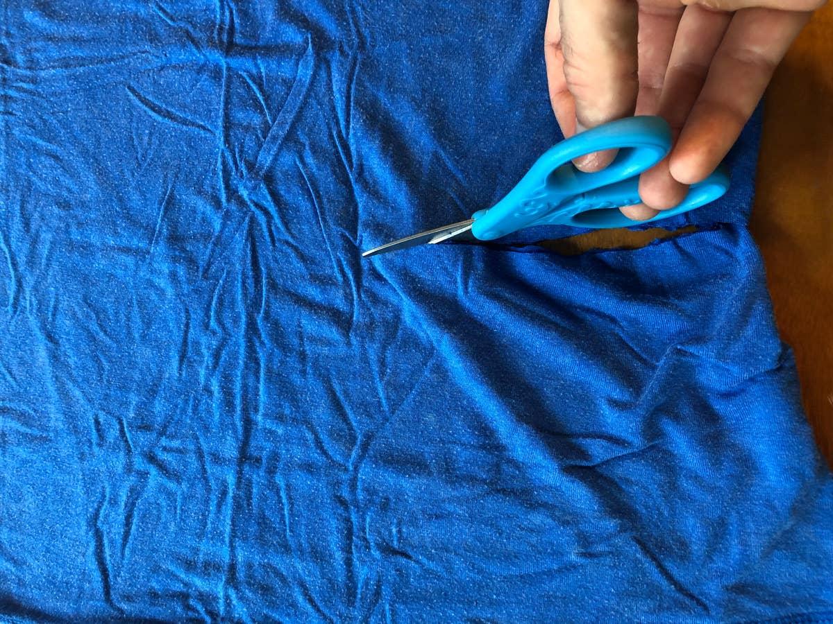 Scissors cutting blue shirt