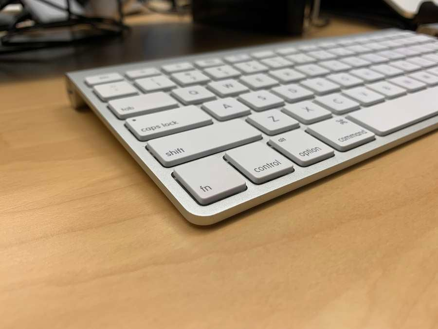 An Apple keyboard on a desk showing fn and control keys