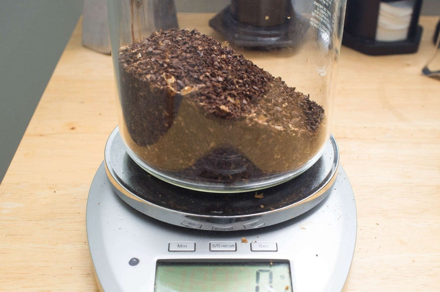 French press coffee maker filled with coffee grounds on a scale