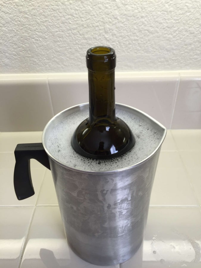 Fill the wine bottle with water and place it in the container