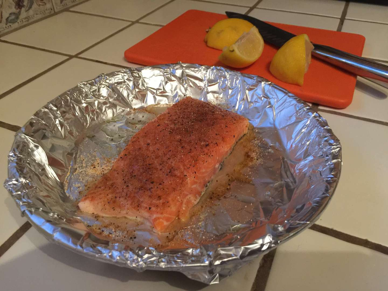 A salmon filet being seasoned