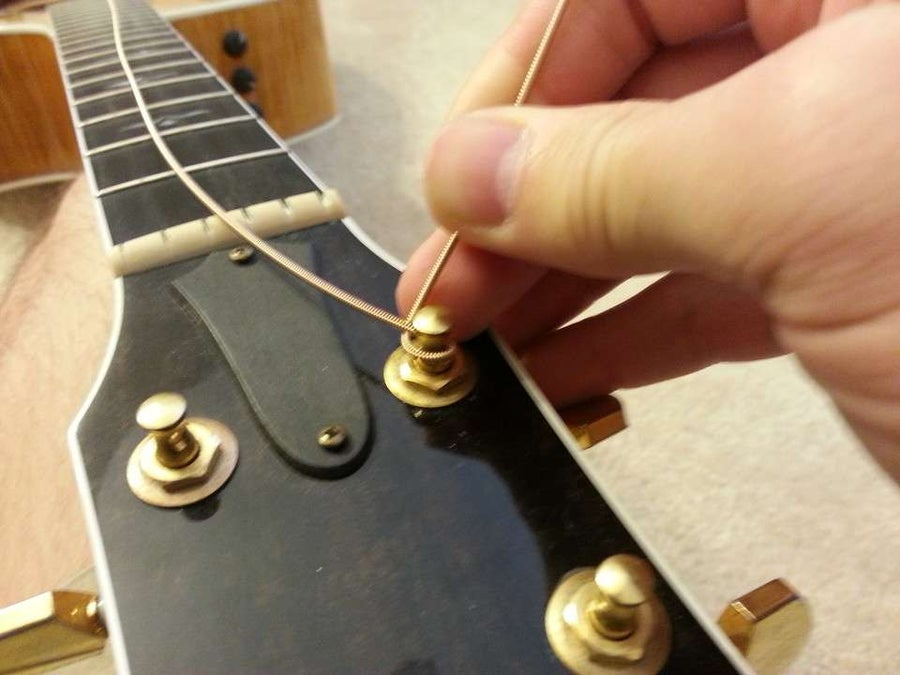 Pull the string behind the tuner then underneath the string