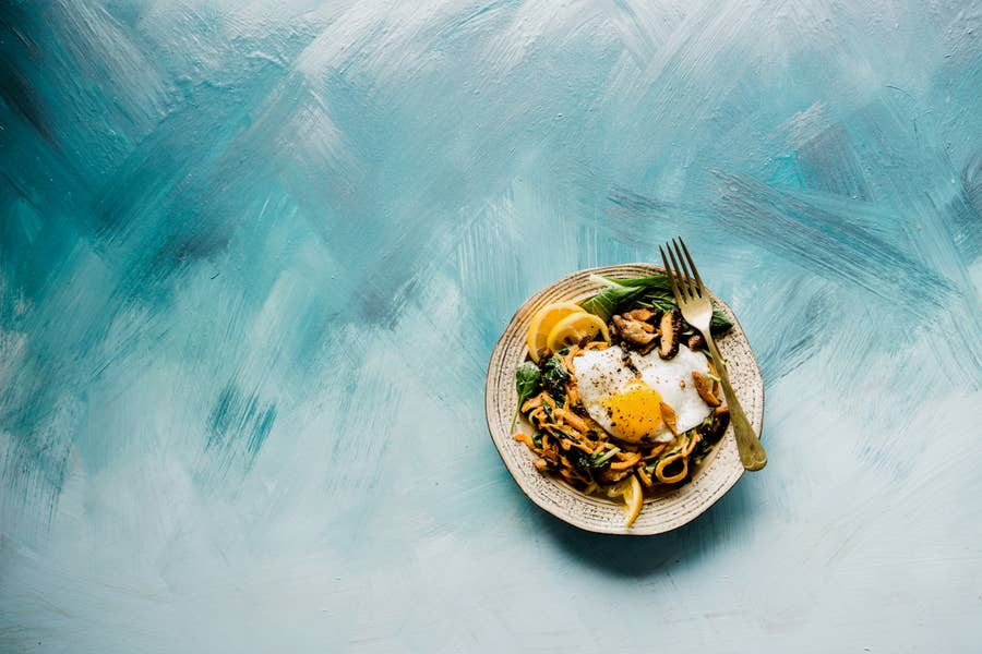 A dish of egg and vegetables on a blue painted background