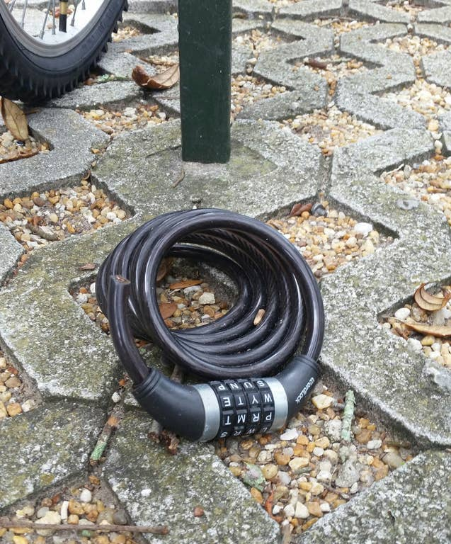 A cut bicycle lock sitting on the ground