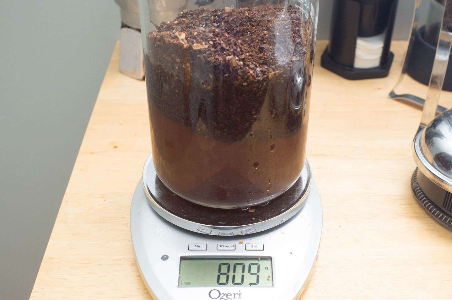 French press coffee maker filled with coffee and water on a scale